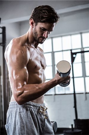 Fit shirtless man lifting dumbbells Stock Photo - Premium Royalty-Free, Code: 6109-08398065