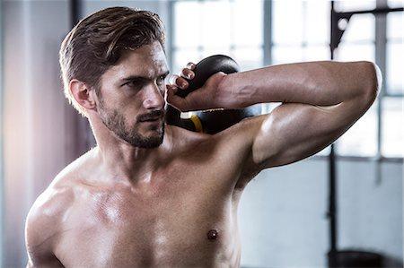 Fit shirtless man lifting kettlebell Stock Photo - Premium Royalty-Free, Code: 6109-08398068
