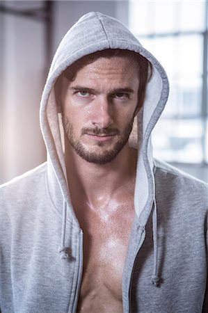 Fit shirtless man with hooded jumper Stock Photo - Premium Royalty-Free, Code: 6109-08398076