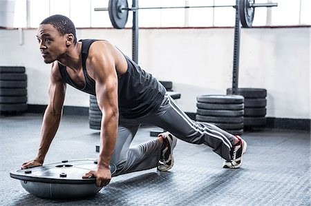 Fit man working out with bosu ball Stock Photo - Premium Royalty-Free, Code: 6109-08398092