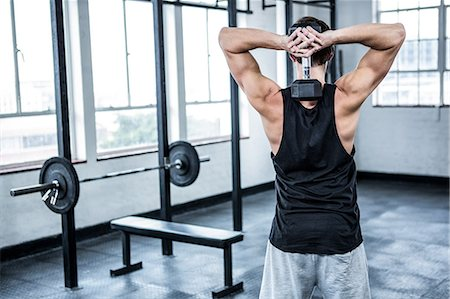 Fit man lifting heavy black dumbbell Stock Photo - Premium Royalty-Free, Code: 6109-08398006