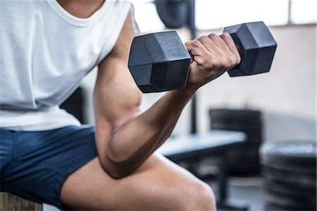 Fit man lifting heavy black dumbbells Stock Photo - Premium Royalty-Free, Code: 6109-08398113