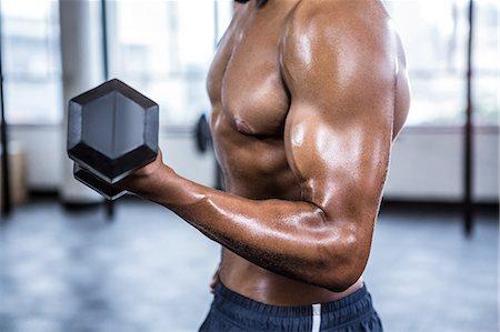 Fit man lifting heavy black dumbbells Stock Photo - Premium Royalty-Free, Code: 6109-08398115