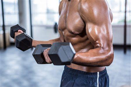 Fit man lifting heavy black dumbbells Stock Photo - Premium Royalty-Free, Code: 6109-08398116