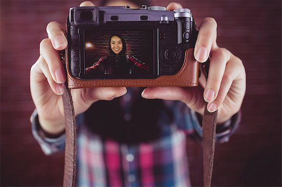 Attractive smiling hipster doing a selfie Stock Photo - Premium Royalty-Free, Image code: 6109-08398215