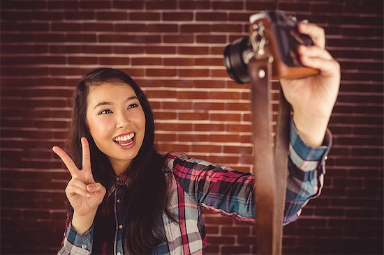 Attractive hipster taking selfie with camera Stock Photo - Premium Royalty-Free, Image code: 6109-08398221