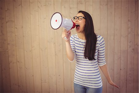 Beautiful woman shouting with megaphone Stock Photo - Premium Royalty-Free, Code: 6109-08398344
