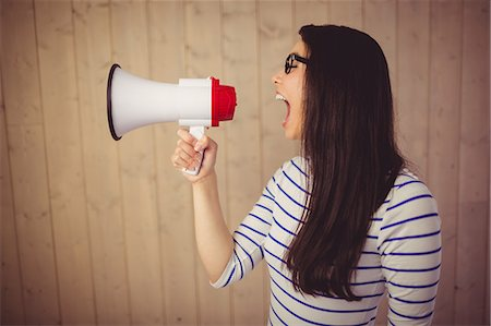 Beautiful woman shouting with megaphone Stock Photo - Premium Royalty-Free, Code: 6109-08398345