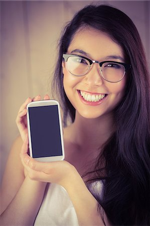 Attractive hipster showing her smartphone Stock Photo - Premium Royalty-Free, Code: 6109-08398305