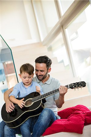 Father teaching son to play guitar Stock Photo - Premium Royalty-Free, Code: 6109-08398848