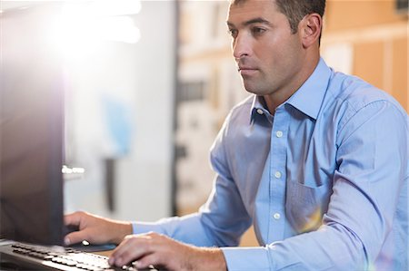 Serious businessman working on computer Stock Photo - Premium Royalty-Free, Code: 6109-08399393