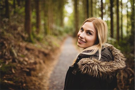 Beautiful blonde woman walking on road surrounded by forest Stock Photo - Premium Royalty-Free, Code: 6109-08481683