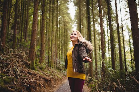 Beautiful blonde woman with arms outstretched in the woods Stock Photo - Premium Royalty-Free, Code: 6109-08481687