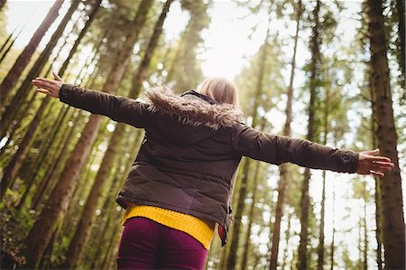 Beautiful blonde woman with arms outstretched in the woods Stock Photo - Premium Royalty-Free, Code: 6109-08481684