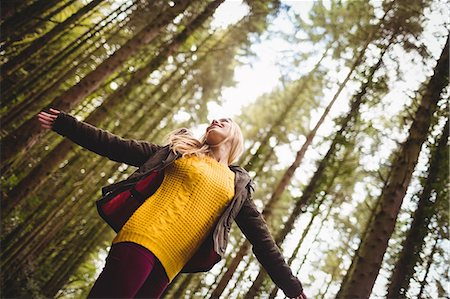 Beautiful blonde woman with arms outstretched in the woods Stock Photo - Premium Royalty-Free, Code: 6109-08481685