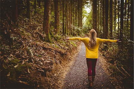 Beautiful blonde woman with arms outstretched in the woods Stock Photo - Premium Royalty-Free, Code: 6109-08481688