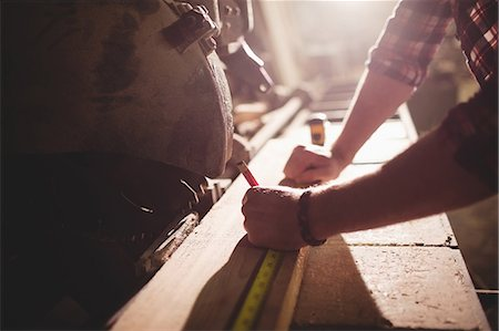 Carpenter working on his craft in a dusty workshop Stock Photo - Premium Royalty-Free, Code: 6109-08481887