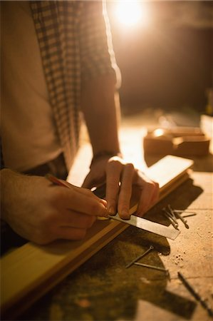 Carpenter working on his craft in a dusty workshop Stock Photo - Premium Royalty-Free, Code: 6109-08481971