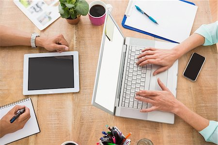 Colleagues using laptop and taking notes in the office Stock Photo - Premium Royalty-Free, Code: 6109-08488639