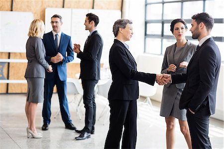 reaching - Business people standing and talking at the office Stock Photo - Premium Royalty-Free, Code: 6109-08488842