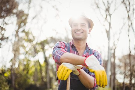 Gardener man posing with his rake in the garden Stock Photo - Premium Royalty-Free, Code: 6109-08489095