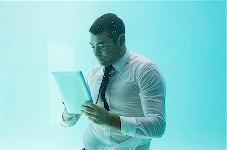 swimming - Businessman using tablet pc underwater in swimming pool Stock Photo - Premium Royalty-Free, Code: 6109-08489757
