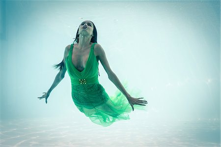 Brunette in evening gown swimming in pool underwater Stock Photo - Premium Royalty-Free, Code: 6109-08489773