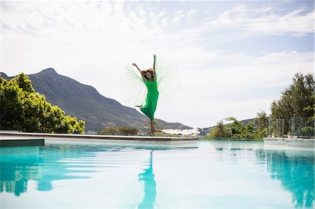 photografia - Elegant woman dancing by the pool on a summers day Foto de stock - Royalty Free Premium, Número: 6109-08489770