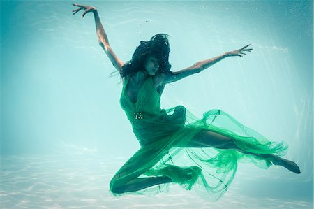 photografia - Brunette in evening gown swimming in pool underwater Foto de stock - Royalty Free Premium, Número: 6109-08489772