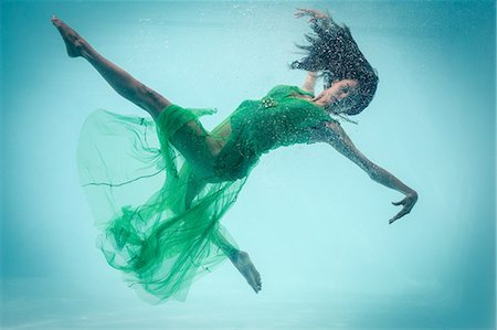 photografia - Brunette in evening gown swimming in pool underwater Foto de stock - Royalty Free Premium, Número: 6109-08489775