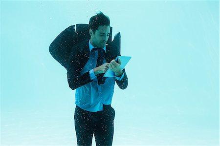 scroll - Businessman using tablet underwater in swimming pool Stock Photo - Premium Royalty-Free, Code: 6109-08489776