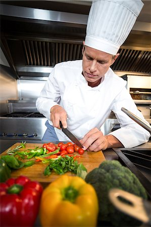 Chef preparing vegetables at counter in a commercial kitchen Stock Photo - Premium Royalty-Free, Code: 6109-08489851