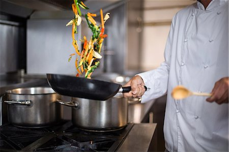 Chef making a stir fry in a commercial kitchen Stock Photo - Premium Royalty-Free, Code: 6109-08489855