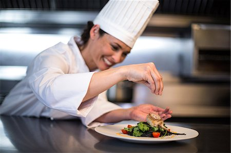 Happy chef seasoning her dish in a commercial kitchen Stock Photo - Premium Royalty-Free, Code: 6109-08489861