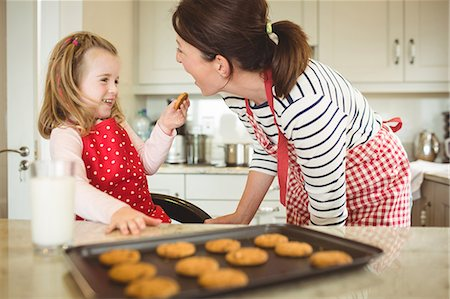 Daughter feeding cookie to mother in kitchen Stock Photo - Premium Royalty-Free, Code: 6109-08434660