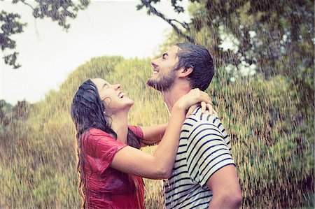 Handsome man carrying his girlfriend under the rain in the park Stock Photo - Premium Royalty-Free, Code: 6109-08434618