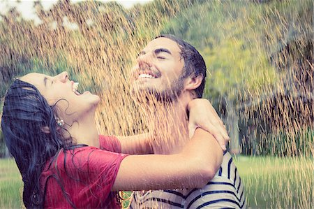 Cute couple hugging under the rain in the park Stock Photo - Premium Royalty-Free, Code: 6109-08434619