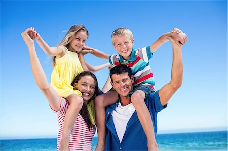 Cute parents giving piggy backs to their children on the beach Stock Photo - Premium Royalty-Free, Code: 6109-08434748