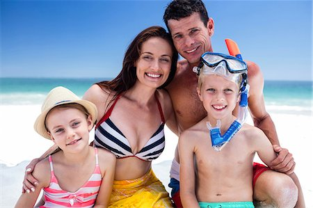 Cute family posing for camera with boy wearing snorkeling equipment on the beach Stock Photo - Premium Royalty-Free, Code: 6109-08434792