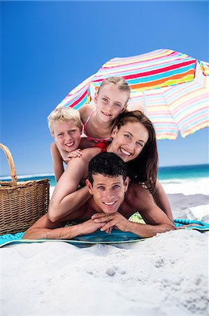 Cute family lying on towels on the beach Stock Photo - Premium Royalty-Free, Code: 6109-08434796