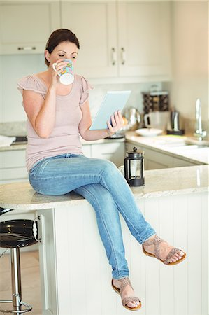 scroll - Woman drinking a cup of coffee while using tablet Stock Photo - Premium Royalty-Free, Code: 6109-08434714