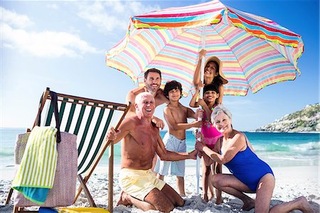 Cute family setting their umbrella on the beach Stock Photo - Premium Royalty-Free, Code: 6109-08434840