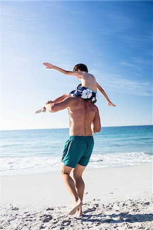 Father giving piggy back to his son on the beach Stock Photo - Premium Royalty-Free, Code: 6109-08434857