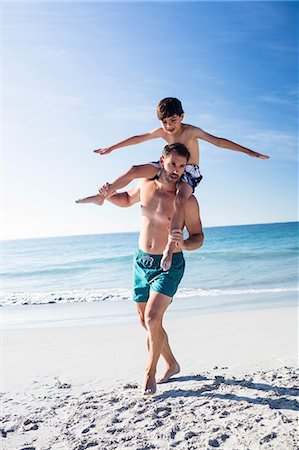 Father giving piggy back to his son on the beach Stock Photo - Premium Royalty-Free, Code: 6109-08434856