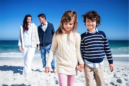 sister - Cute siblings holding hands with parents behind on the beach Stock Photo - Premium Royalty-Free, Code: 6109-08434893