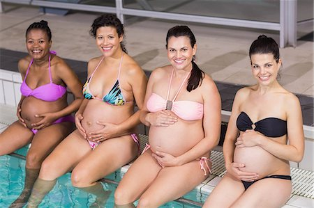 Smiling pregnant women touching their belly at the swimming pool Stock Photo - Premium Royalty-Free, Code: 6109-08434982