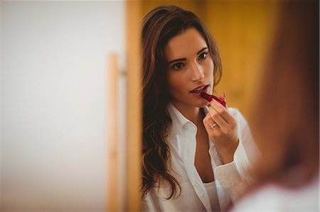 eautiful brunette applyBing lipstick in front of the mirror at home Stock Photo - Premium Royalty-Free, Code: 6109-08435532