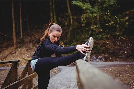 Fit brunette stretching her legs in the woods Stock Photo - Premium Royalty-Free, Code: 6109-08435603