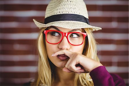 Blonde woman having a fake mustache on brick wall Stock Photo - Premium Royalty-Free, Code: 6109-08435770