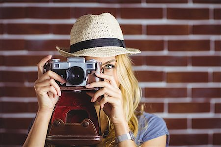 Blonde woman taking picture on brick wall Stock Photo - Premium Royalty-Free, Code: 6109-08435782